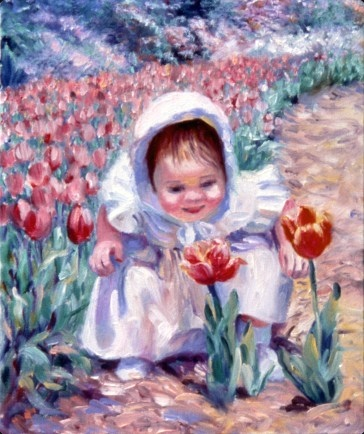 A young girl in a white dress crouches to smell a vibrant red and orange tulip.